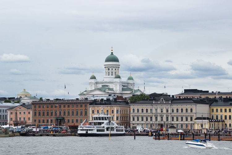 Buildings at waterfront against cloudy sky