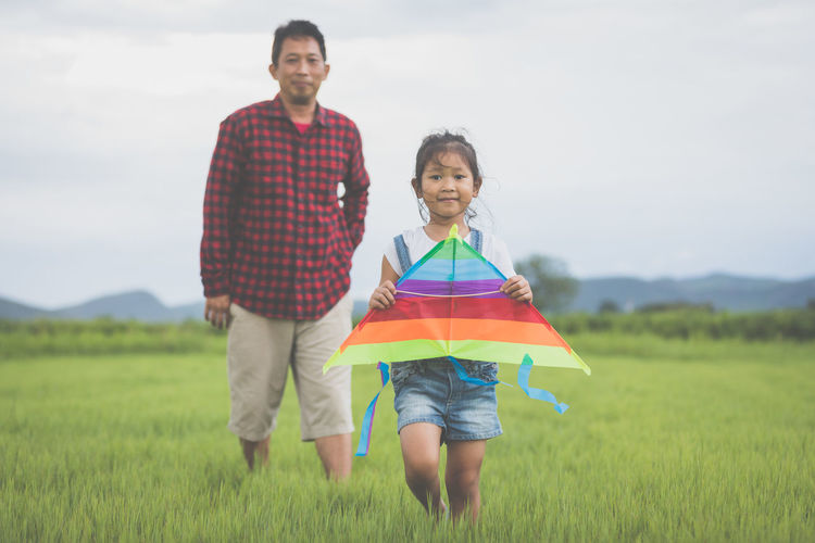Portrait of girl with father holding kite while standing on grassy field