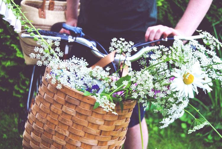 Woman holding bicycle with white flowers in basket