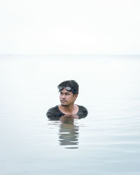 Portrait of young man swimming in sea against clear sky