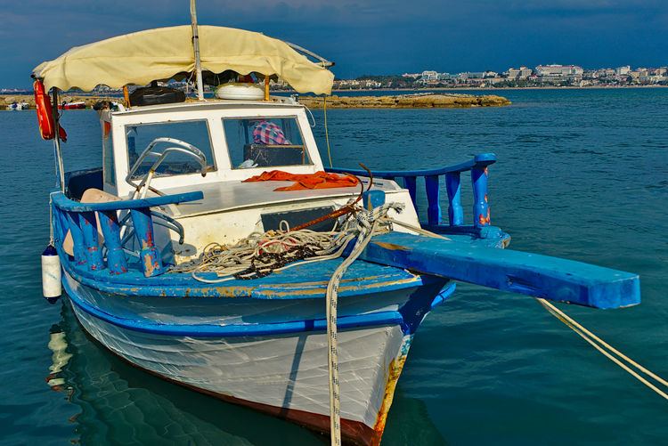 Fishing boats moored on sea against blue sky