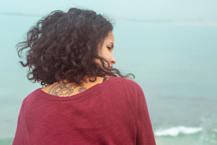 One Person Water Real People Casual Clothing Hair Sea Lifestyles Leisure Activity Hairstyle Portrait Focus On Foreground Women Headshot Curly Hair Day Nature Looking Beach Beautiful Woman Outdoors Contemplation Tattoo