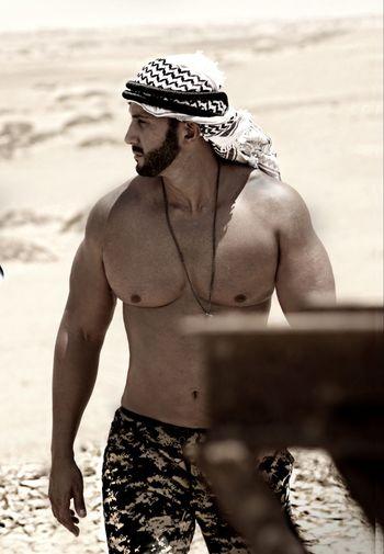 Shirtless man standing in desert during sunny day