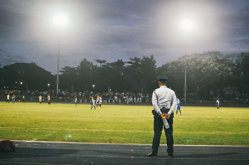 Rear view of security guard looking at players playing soccer on field at night