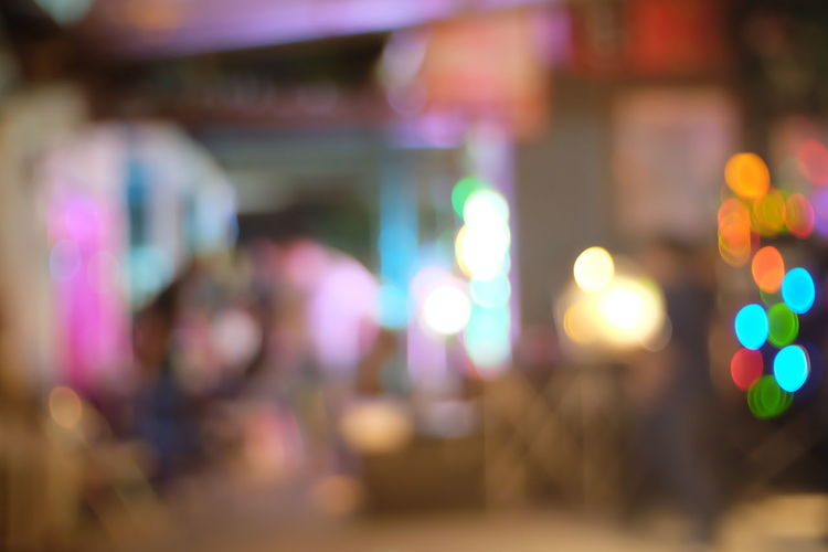 Defocused Illuminated Night Multi Colored City Street Focus On Foreground Incidental People Lighting Equipment Light - Natural Phenomenon People Outdoors Adult Lens Flare Lifestyles Real People Women Glowing Selective Focus Light