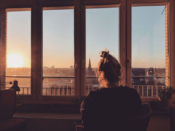 Woman looking through window at sunset