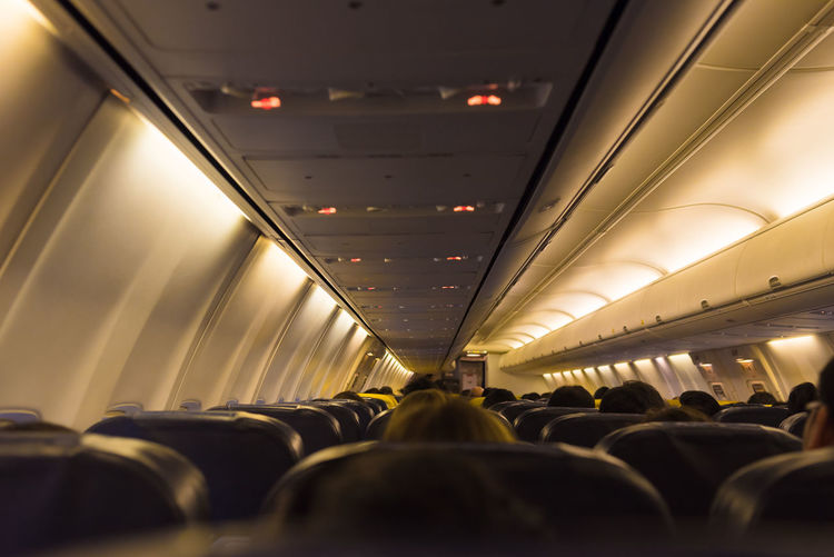 Passengers Sitting In Illuminated Airplane