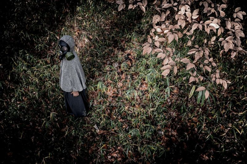 High angle view of person wearing gas mask while standing on grassy field in forest