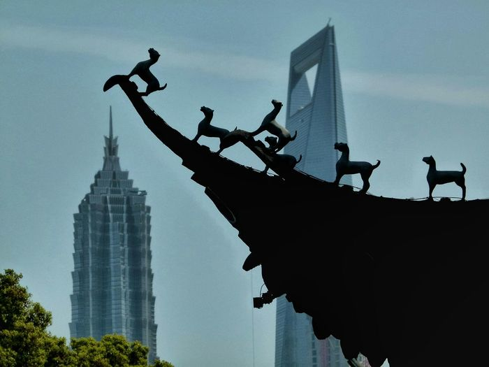 Low angle view of dog sculpture against modern office skyscrapers