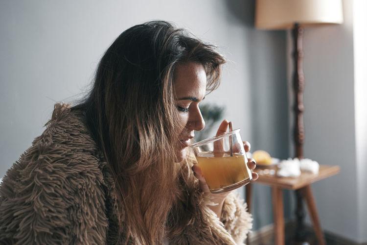 Close-up of woman drinking lemon tea sitting on bed