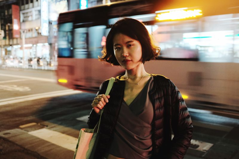 Portrait of young woman standing against bus on road in illuminated city at night