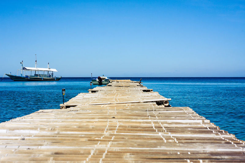 Sailboats on pier by sea against clear blue sky
