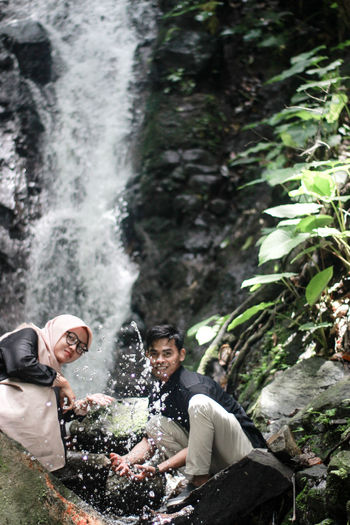 Man and woman splashing water against waterfall in forest