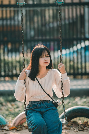 Young woman standing on swing at playground