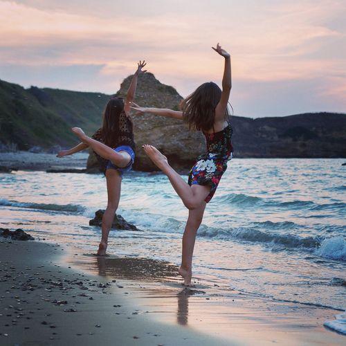 Teenage Girls Standing On One Leg At Beach