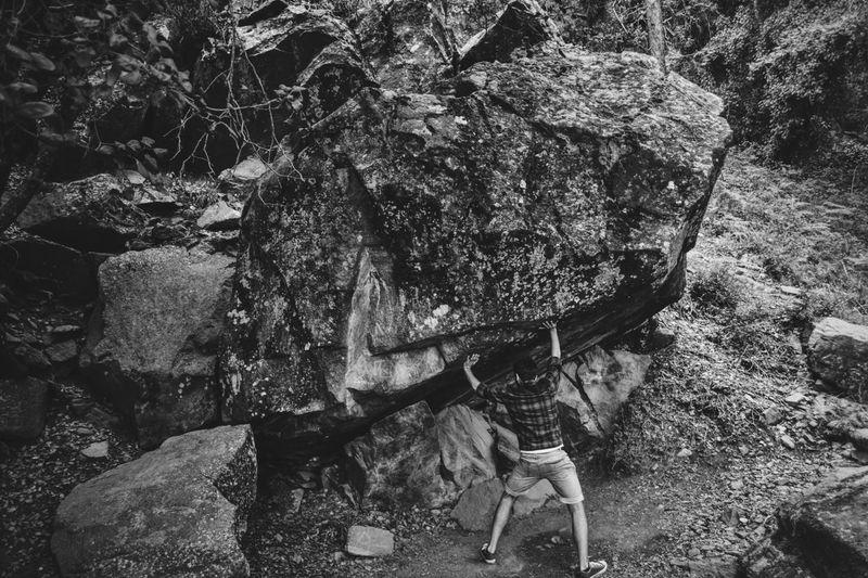 Optical illusion of man pushing boulder rock