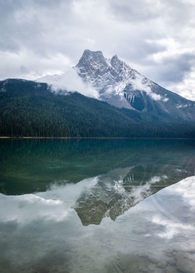 Mountain shrouded with clouds reflected in still waters of a lake, emerald lake, yoho np, bc, canada