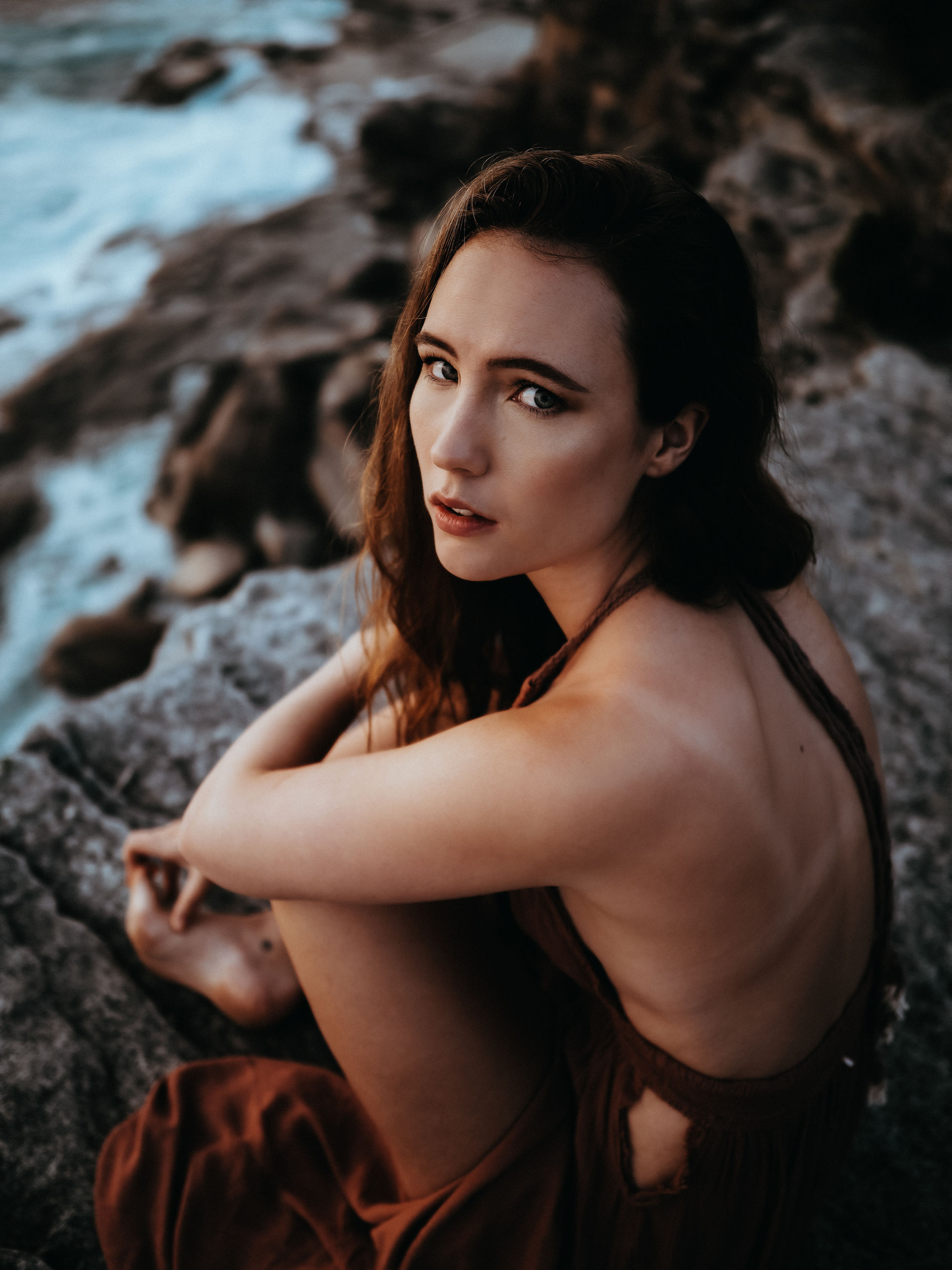 female, one person, women, adult, young adult, portrait, portrait photography, hairstyle, rock, land, long hair, photo shoot, water, looking at camera, nature, sitting, fashion, clothing, brown hair, beauty in nature, sea, beach, relaxation, dress, person, contemplation, looking, outdoors, serious, side view, dusk, focus on foreground, solitude, tranquility, emotion