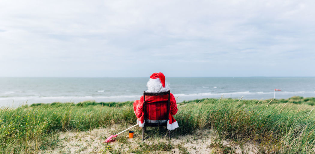 Back view of santa claus on a trip to the sea enjoying the view from a dune sitting on a deckchair