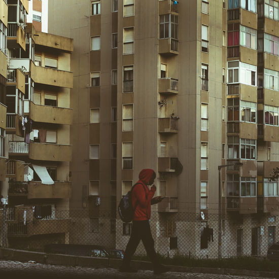 Rear view of man standing by building in city