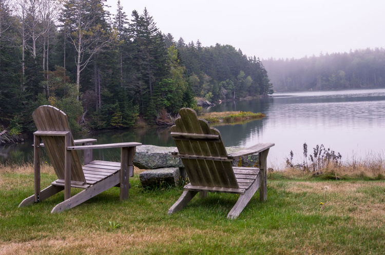 View of the water over the back of a pair of Adirondack chairs. Adirondack Chairs Beauty In Nature Chair Day Grass Lake Nature No People Outdoors Rear View Relaxation Scenics Sky Tranquil Scene Tranquility Tree Water