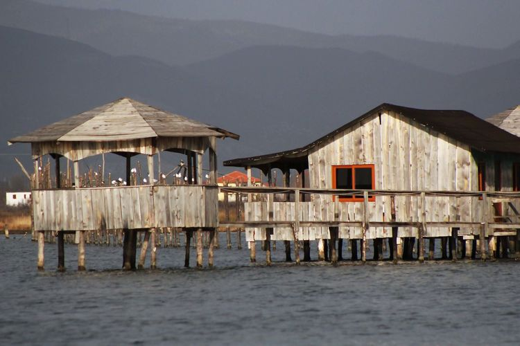 Stilt House On Sea By Building Against Sky