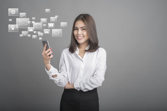 Business Business Businesswoman Chats Communication Connection Finance Front View Global Communications Globalization Gray Background Internet Looking At Camera One Person Smart Phone Smiling Standing Studio Shot Talking Photo Tech Technology Touch Screen Touching Women Young Adult