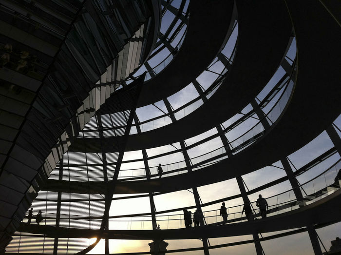 Low angle view of people walking in reichstag at sunset
