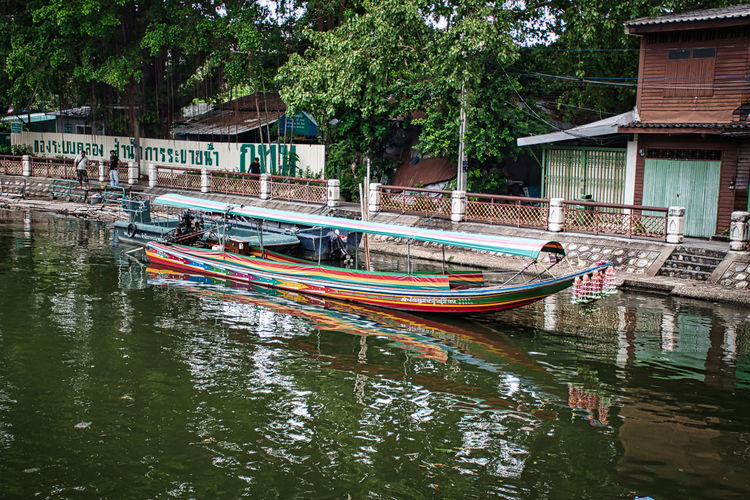 Boats moored in canal by trees