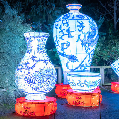 Close-up of illuminated lantern against blue wall