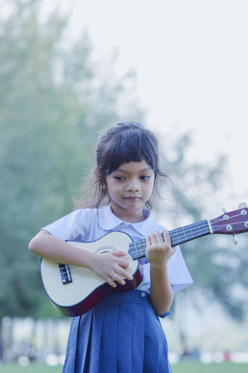 Girl playing ukulele while standing at park