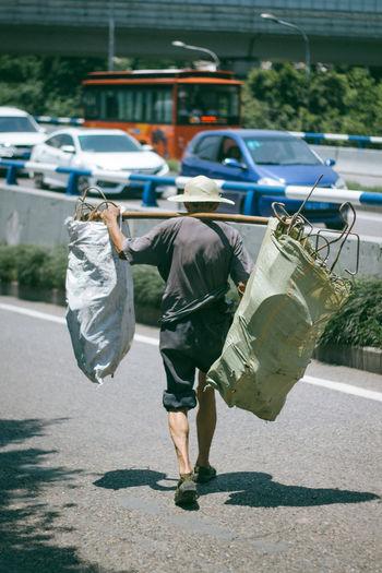 Rear view of man carrying metal in sacks on street