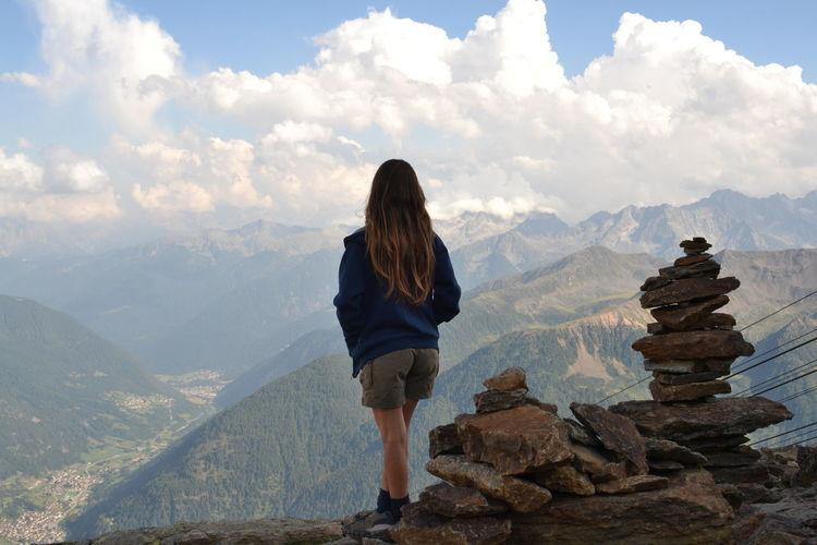 Girl standing on rock against sky