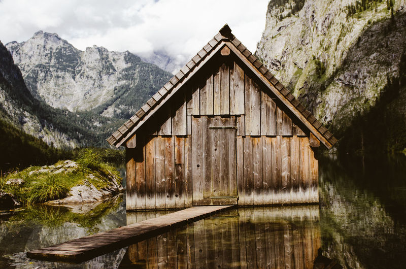 Log Cabin In Lake Against Mountains
