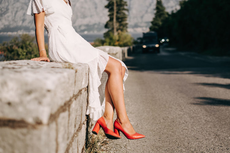 Women leg with red shoes sitting on the road