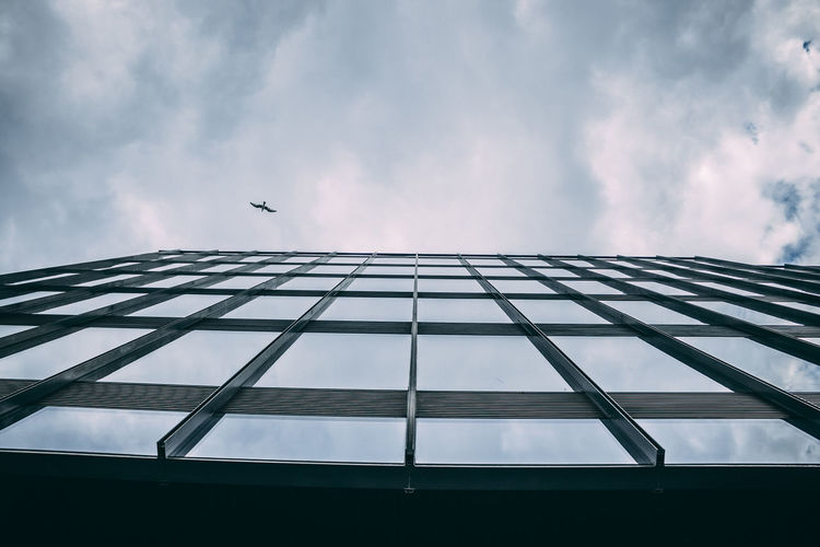 Low angle view of bird flying over building against cloudy sky