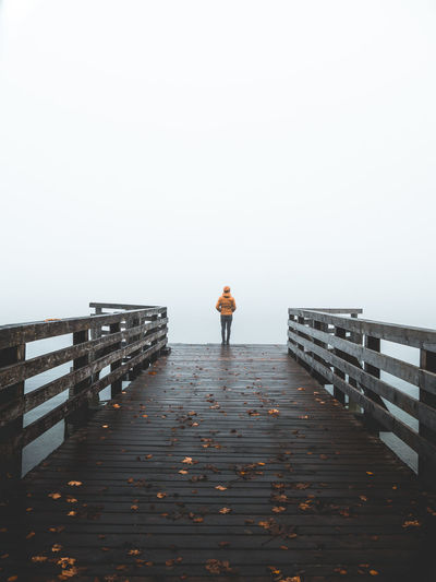 Rear view of man standing on pier during foggy weather