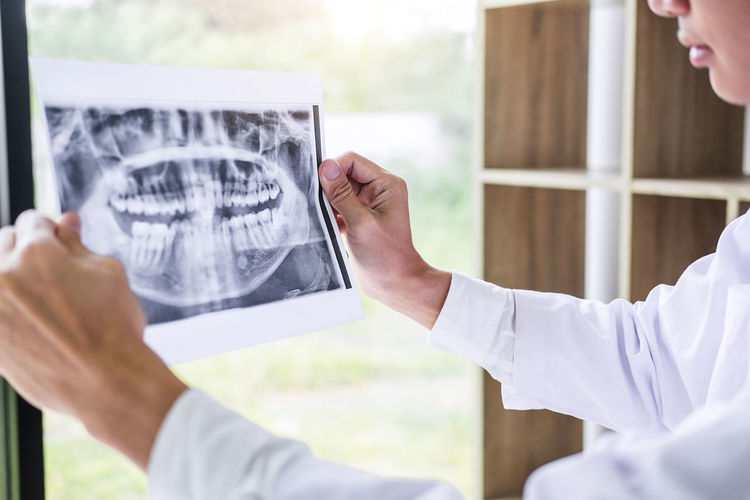 Dentist Analyzing X-Ray At Clinic