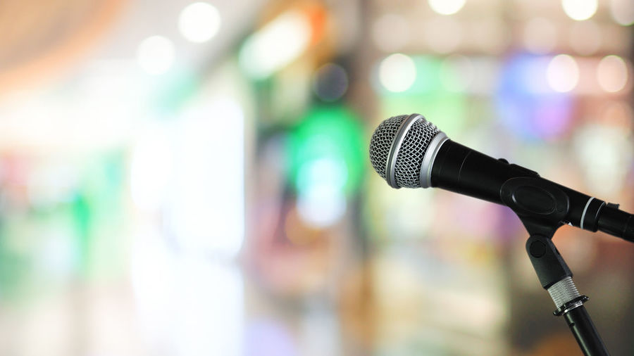 Microphone with blurred bright light background and selective image for business technology communication concepts Concert Electrical Equipment Nightlife Stage Conference - Event Anticipation Illuminated Performance Musical Instrument Absence Communication Sound Recording Equipment Selective Focus No People Equipment Technology Close-up Arts Culture And Entertainment Microphone Stand Indoors  Audio Equipment Music Focus On Foreground Microphone Input Device Indoors  Stage - Performance Space