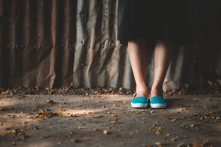 Woman standing wearing blue shoes. Woman Standing Wearing Blue Shoes. Adult Body Part Day Fashion Footpath Human Body Part Human Foot Human Leg Human Limb Leaf Lifestyles Low Section Nature One Person Outdoors Plant Part Real People Shoe Skirt Standing Women
