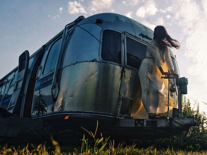 Low Angle View Of Woman Standing On Travel Trailer Against Sky
