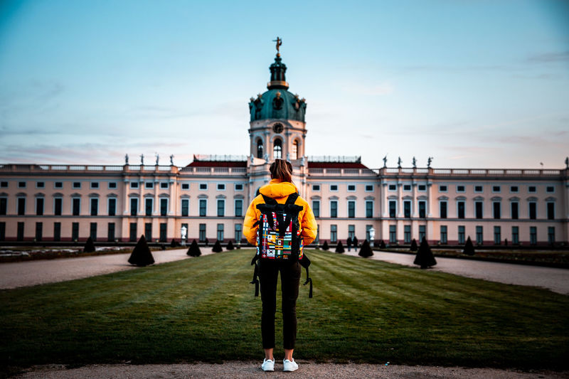Solo female stands in front of palace with backpack with travel flag patches in evening light.