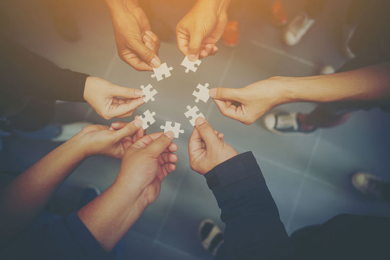 Cropped Image Of Friends Playing Jigsaw Puzzle
