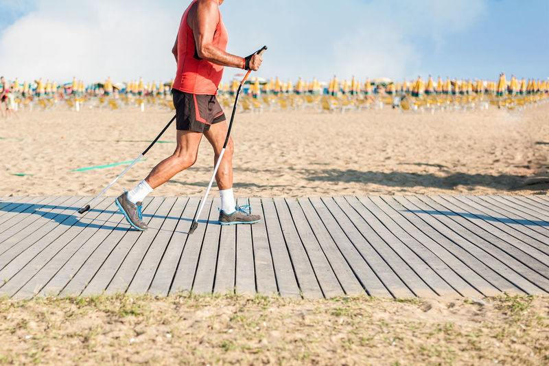 Man hiking with poles on footpath of beach. Holidays Nordic Walking Path Adult Adults Only Athlete Beach Day Exercising Full Length Leisure Activity Lifestyles Men One Person Only Men Outdoors People Pole Sky Sport Sportsman Walking