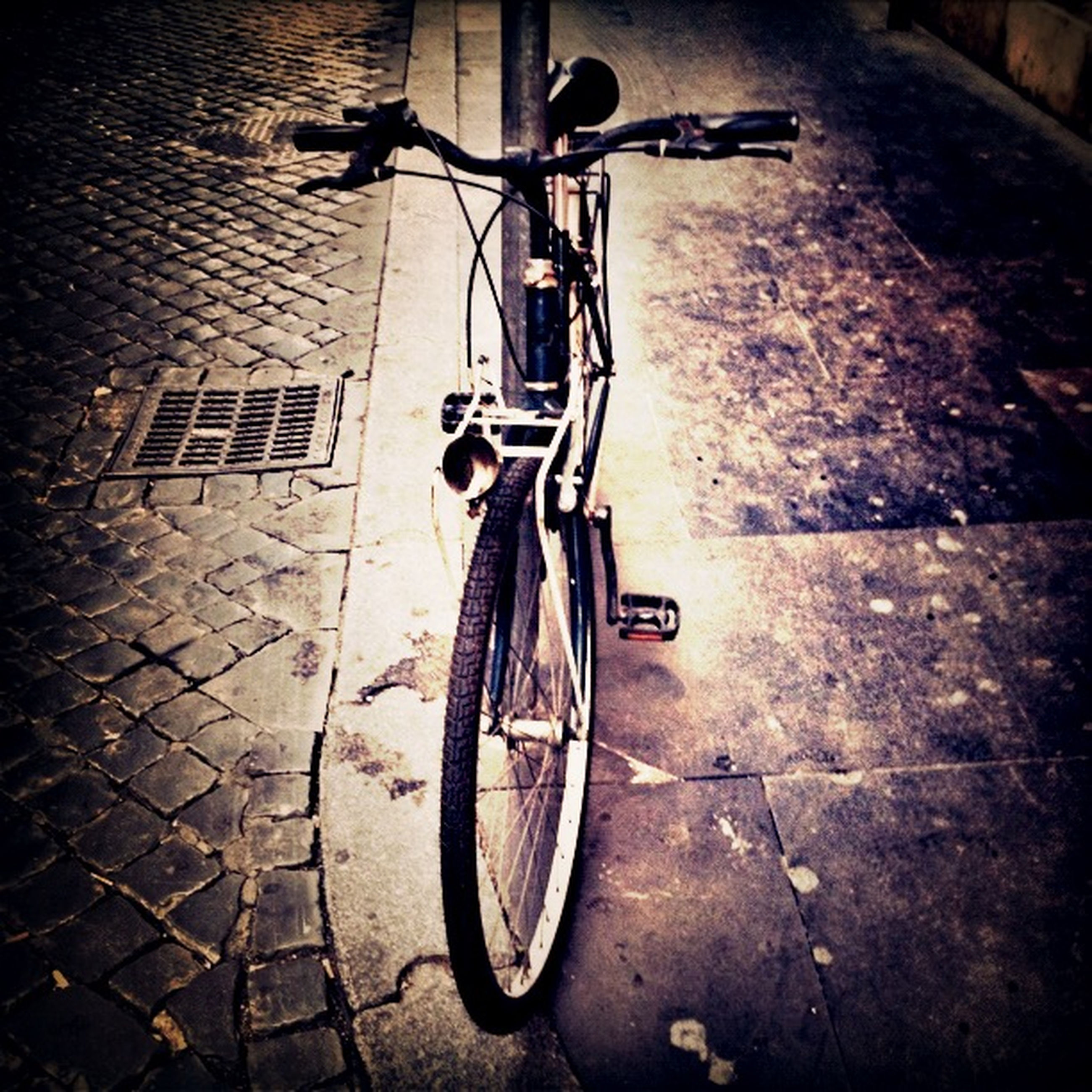 bicycle, transportation, mode of transport, land vehicle, stationary, parked, parking, street, wheel, road, outdoors, travel, day, sidewalk, no people, cobblestone, built structure, cycle, building exterior, sunlight