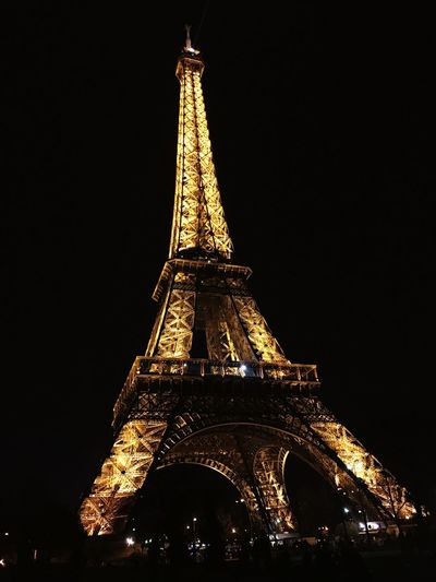Paris Eiffel Tower Tower Architecture Tall - High Night Low Angle View Travel Destinations Built Structure Tourism Illuminated Copy Space History Building Exterior No People Travel Outdoors Celebration Gold Colored City Clear Sky Sky First Eyeem Photo