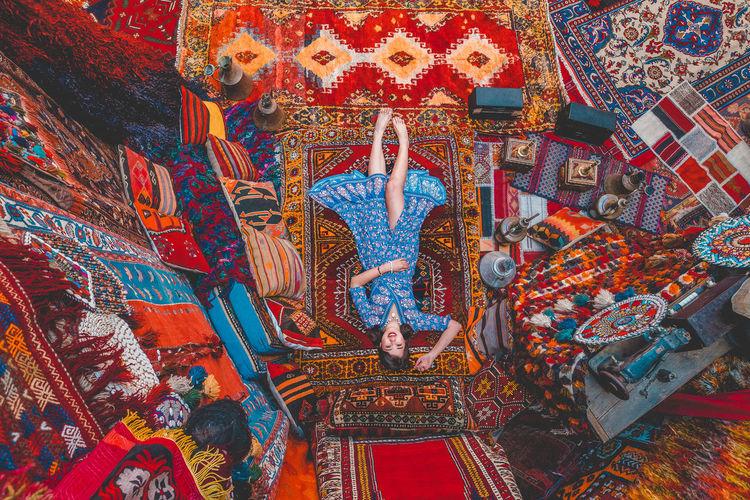 Portrait of woman lying on carpet in store