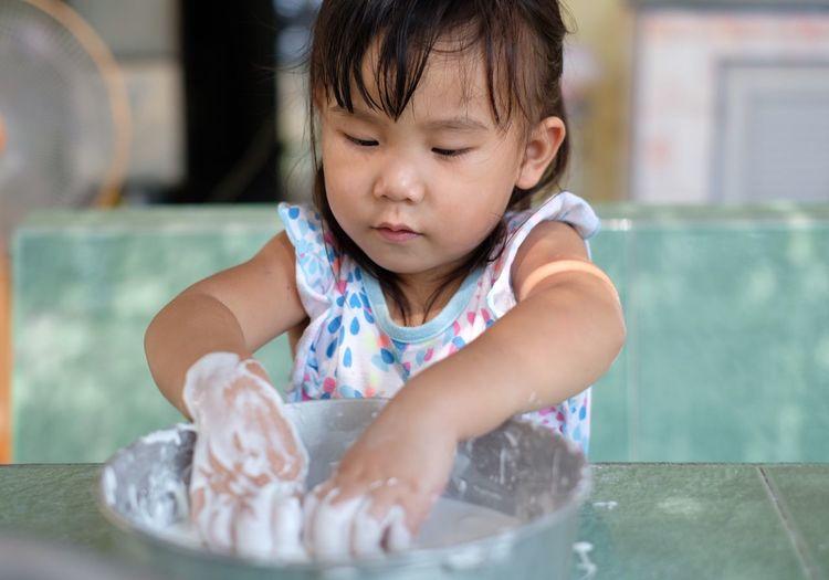 Girl preparing dough at table