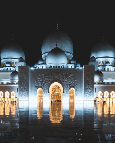 Close-up of illuminated mosque against building at night