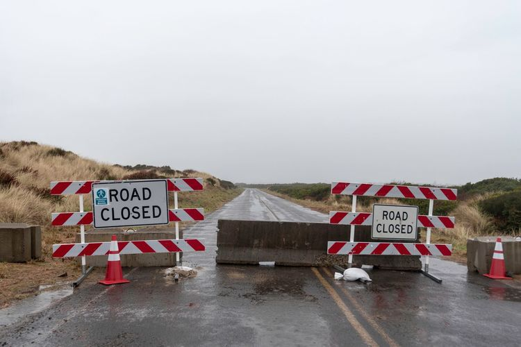 Landscape of 'Road Closed' signs and concrete barriers on a road in Oregon End Of The Line Road Closed Sign Oregon Foggy Road Closed Road Text Communication Western Script Sky Sign Copy Space Nature Day No People Outdoors Land Road
